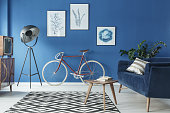 Cozy blue and white loft interior with sofa and bicycle