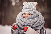 dreamy cozy outdoor portrait of toddler child girl in winter, wearing red gloves, grey knitted hat and scarf