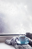 cozy soft gray blanket with a blue cup of coffee on the background of a window decorated with rain drop warming moments winter holidays