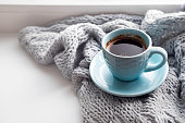 cozy soft gray blanket with a blue cup of coffee on the background of a window warming moments winter holidays