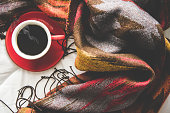 Cozy winter home background, cup of hot coffee with marshmallow, warm knitted sweater on white bed background, vintage tone.  Lifestyle concept