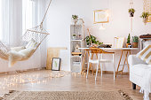 Cozy working place in the white room with hammock