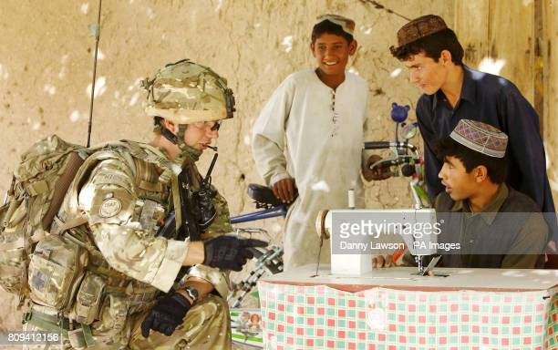 Cpl Alan Hiddleston of XRay Company 45 Commando Royal Marines with locals in the village of Siadabad while on patrol from Patrol Base Kalang in...