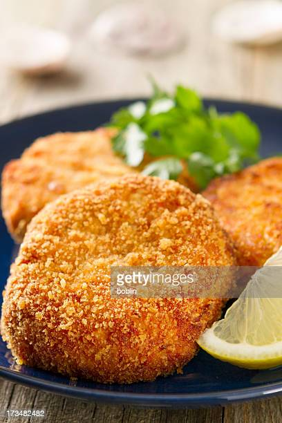 Crab cakes on a blue plate with lemon wedge