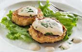 Homemade crab cakes with creamy mustard sauce and fresh parsley are a delicious entree.