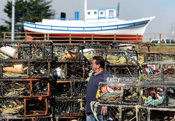 A crab fisherman inspects his crab traps that are stacked at the Pillar Point Harbor parking lot November 15 2007 in Princeton By The Sea California...