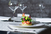 Exclusive food, haute cuisine served in restaurant interior. Crab meat appetizer on white plate. Seafood delicacy