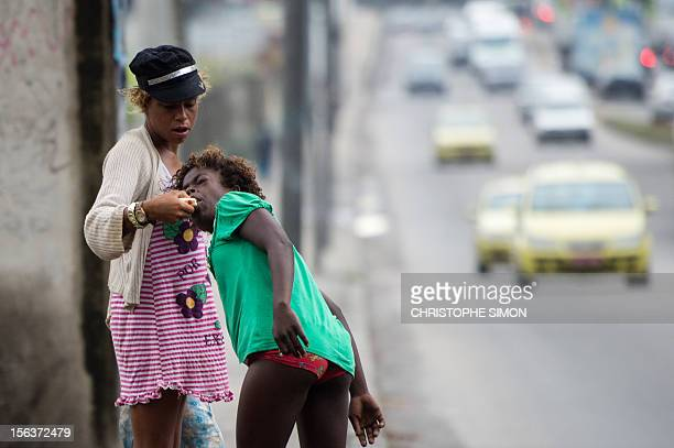A crack addict gives bread to another in the surroundings of Parque Uniao slum in Rio de Janeiro Brazil as social workers and the police carry out an...