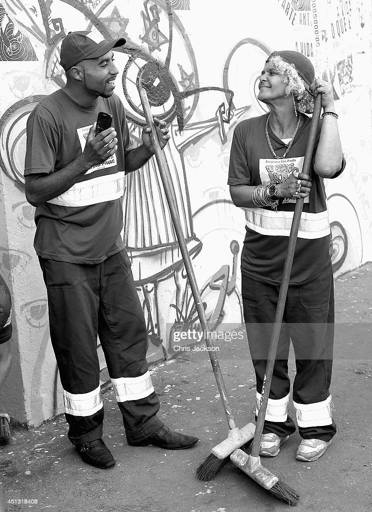 Crack addict street cleaners listen to music ahead of Prince Harry's visit to 'Cracolandia', an extremely deprived area of Sao Paulo with a high concentration of crack addicts on June 26, 2014 in Sao Paulo Brazil. Crack in Sao Paulo costs just 80 UK pence for a rock of the drug. Prince Harry is on a four day tour of Brazil that will be followed by Two days in Chile.