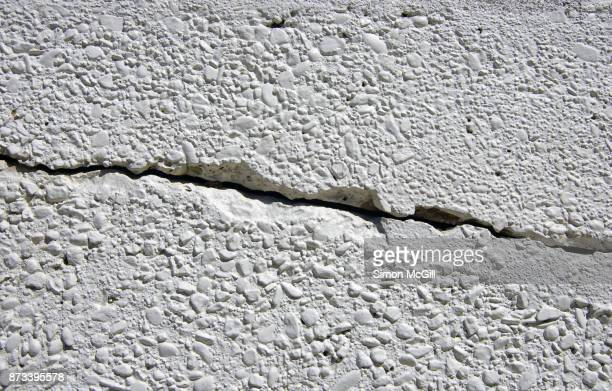 Crack in a painted exposed aggregate gravel concrete wall