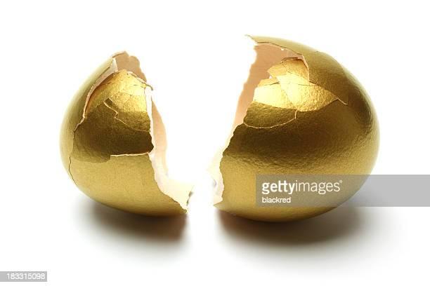 Crack abierto huevos de oro sobre fondo blanco
