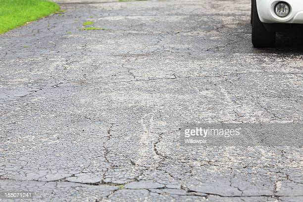 Cracked asphalt driveway with car parked