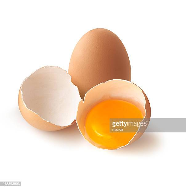 A cracked, brown egg next to a whole one