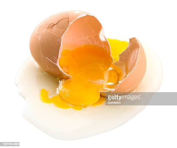 Cracked brown eggs with yolk spilling out