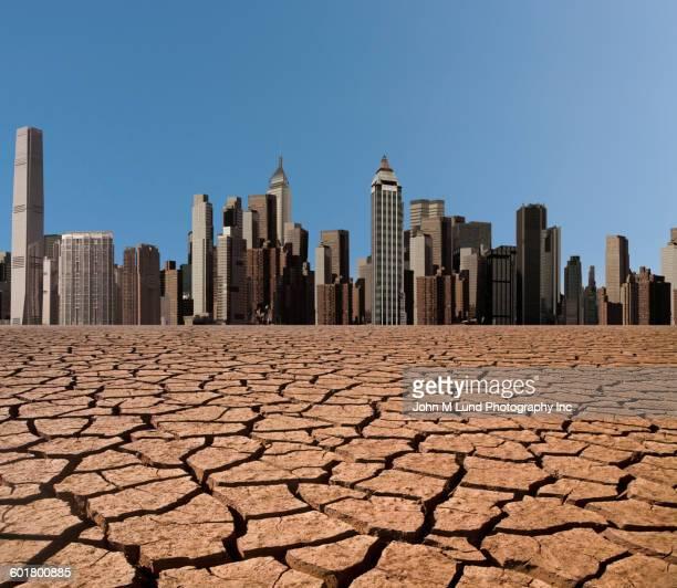 Cracked desert earth outside cityscape