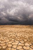 Cracked earth under cloudy sky in desert landscape