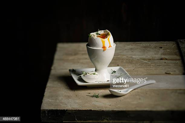 Cracked egg in egg cup with cress and spoon, close up