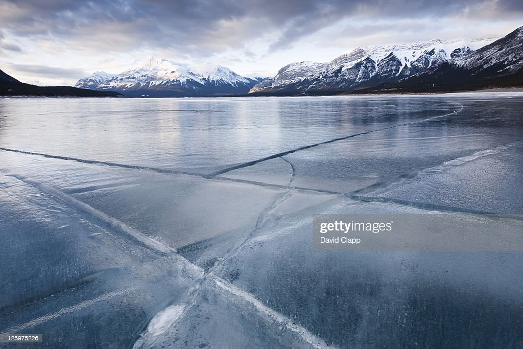 Cracked ice on frozen glacial lake, Abraham Lake, Canadian Rockies, Alberta, Canada