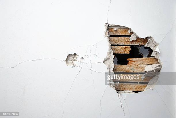 Cracked plaster, drywall and wood of a home's white wall