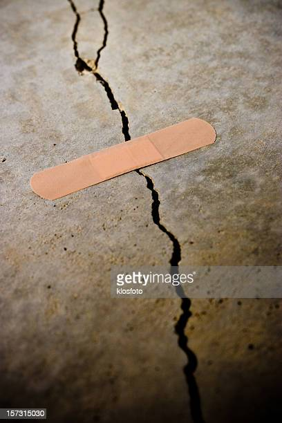 A cracked surface with a band aid