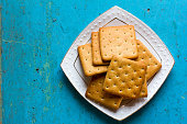Cracker biscuits in a white ceramic square saucer on old blue background close-up. Free space for text. Copy space.Top view
