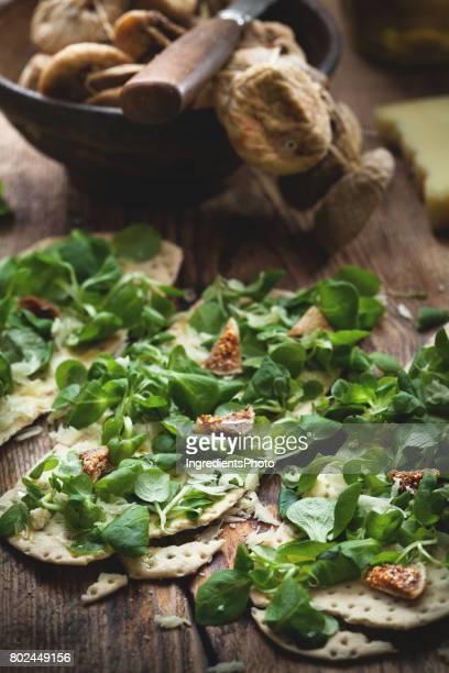 Craquelins avec salade figues séchées et parmesan sur la table en bois.