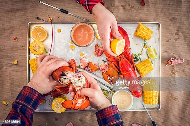 Cracking and Eating Delicious Cooked Lobster with Seafood Utensil