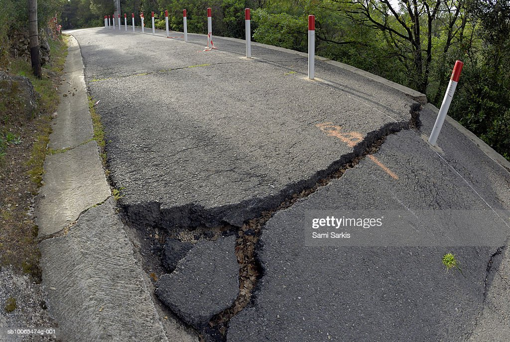 Cracks on countryside road after ground slippage (wide angle lens) : Stock Photo