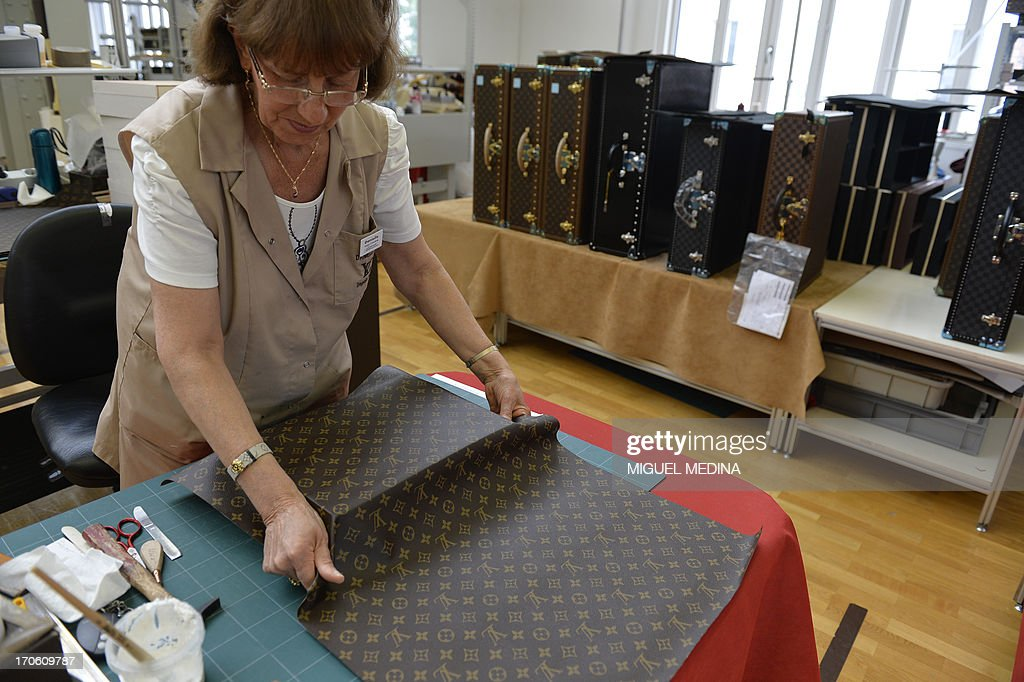A crafstwoman covers a case with leather in the bag workshop of luxury brand Louis Vuitton, part of France-based luxury goods company LVMH Moet Hennessy Louis Vuitton SA, in Asnieres-sur-Seine near Paris on June 15, 2013.