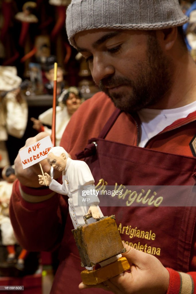 Craftman Gennaro Di Virgilio works on a Christmas figurine depicting Pope Benedict XVI holding a placard reading in German 'Goodbye' in his shop in Via San Gregorio Armeno on February 12, 2013. Pope Benedict XVI will bid his followers farewell in a final audience in St Peter's Square on February 27, the day before he officially steps down, a Vatican spokesman said.
