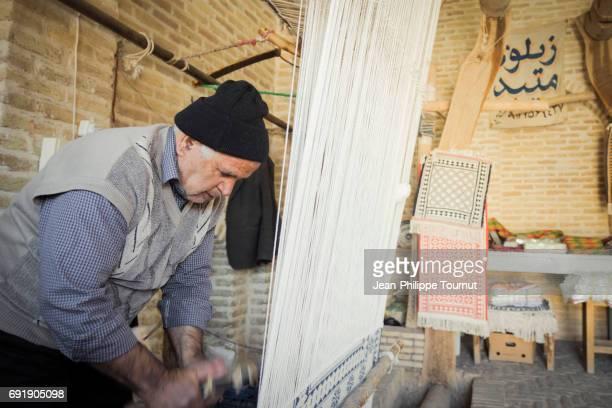 Craftman weaving a carpet in Meybod old Caravanserai, Yazd Province, Central Iran