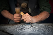 Craftsman hands working on a slate plate