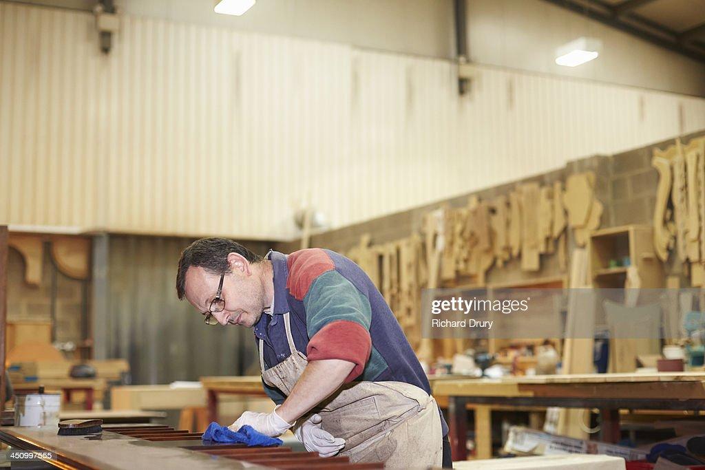 Craftsman applying wax finish to furniture : Stock Photo