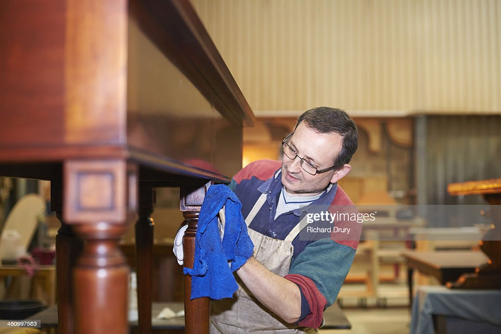 Craftsman applying wax finish to furniture : Stock Photo