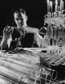 A craftsman at A Gallenkamp and Co makers of laboratory equipment holding a glass condenser coil UK 24th May 1955