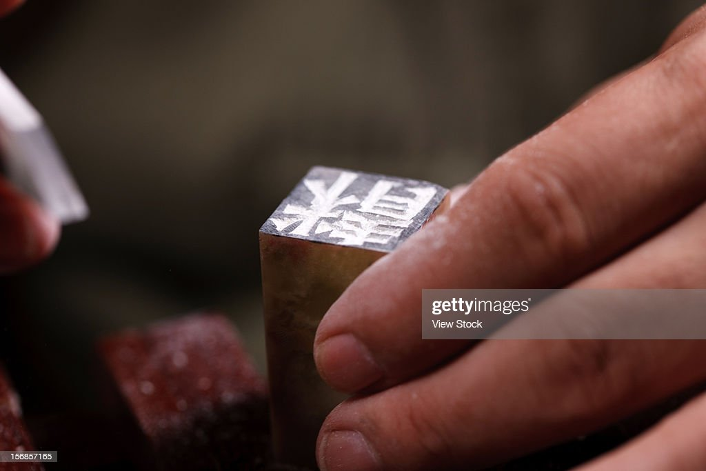 Craftsman carving Chinese character into a Chinese chop : Stock Photo
