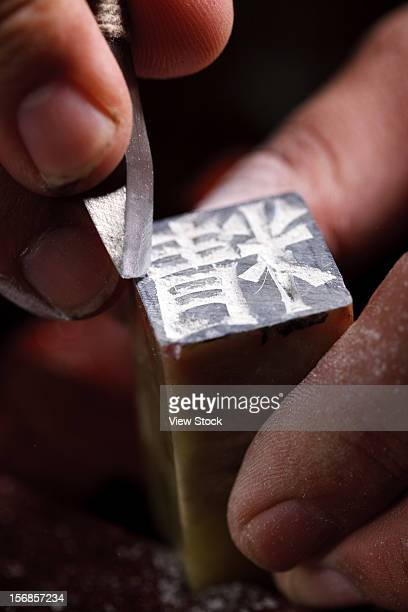 Craftsman carving Chinese character into a Chinese chop