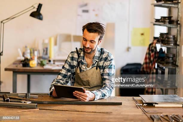 craftsman in metal workshop using tablet