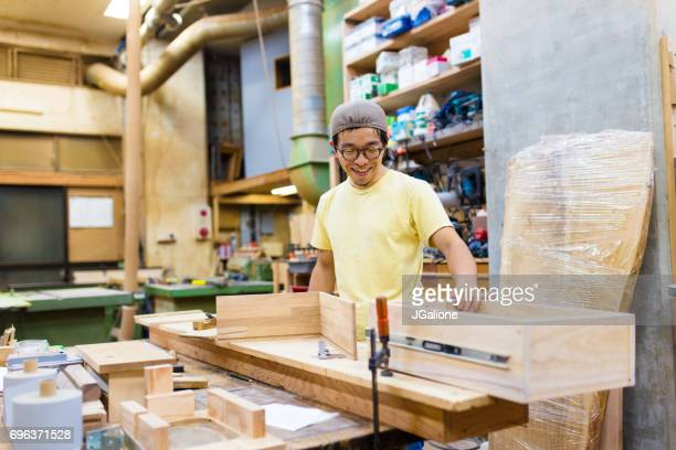 Craftsman inspecting a piece of furniture in his workshop