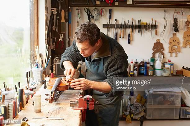 Craftsman polishing violin in repair workshop