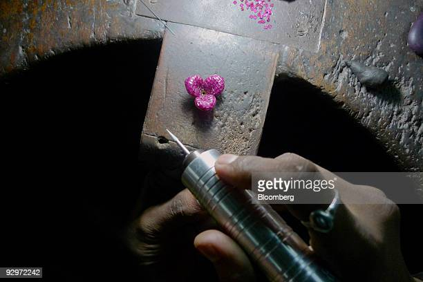 A craftsman puts a gemstone known as a 'ruby diamond' into a gold pendant at a diamond finishing and jewelry workshop in Mumbai India on Tuesday Nov...