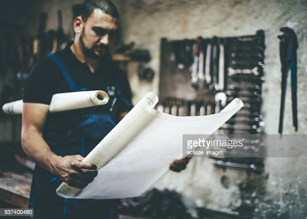 Handwerker lesen Pläne auf seinem Handwerk in seinem Atelier