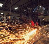 Craftsman sawing metal, sparkles around workshop.