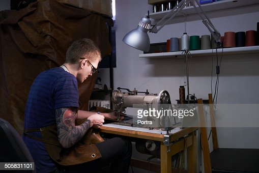 Craftsman using sewing machine to stitch leather