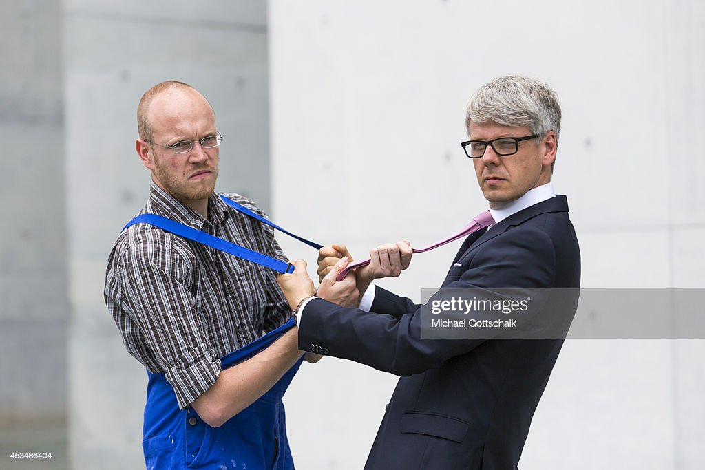 A craftsman wearing a boiler suit and a man wearing a business suit pull on their clothes are an argument on August 07 2014 in Berlin Germany