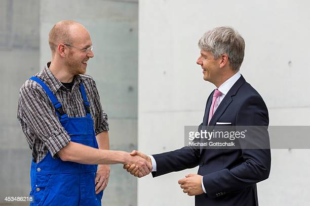 A craftsman wearing a boiler suit and a man wearing a business suit shake hands on August 07 2014 in Berlin Germany
