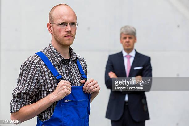 A craftsman wearing a boiler suit and a man wearing a business suit stand next to each other on August 07 2014 in Berlin Germany