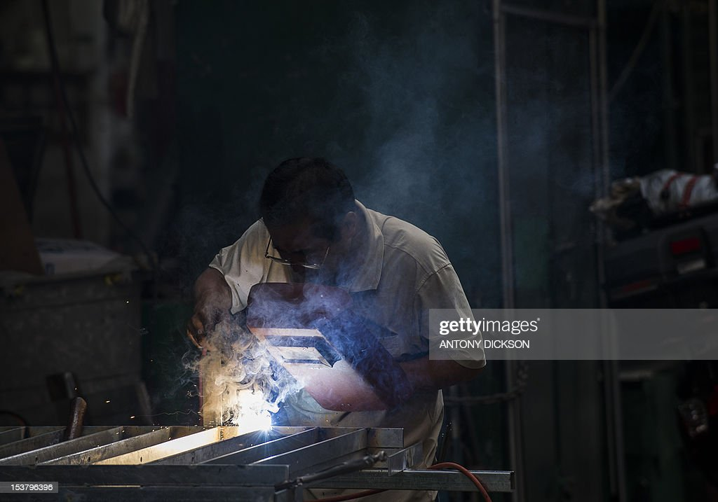 A craftsman welds a fence and hand railing made of galvanised steel in Hong Kong on October 9, 2012. The IMF cut its growth forecasts for developing Asia, blaming a slowdown in Europe and the US, and warned that China's attempts to boost its economy had not taken hold. AFP PHOTO / Antony DICKSON