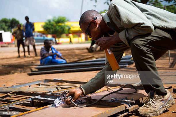 A craftsman welds a metal gate in the Ruashi district of Lubumbashi on December 6 2011 Whilst many people are concerned about outbreaks of violence...