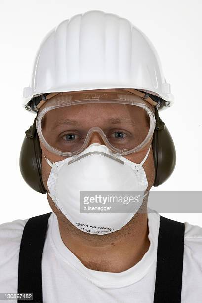 craftsman with protective goggles, face mask, ear protection and helmet